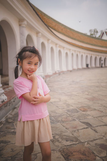 Portrait of smiling girl standing against pink building