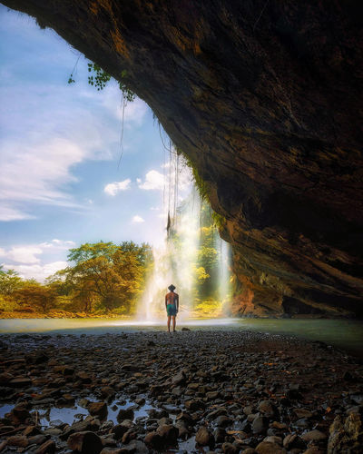 Rear View Of Shirtless Man Standing In Cave By Waterfall