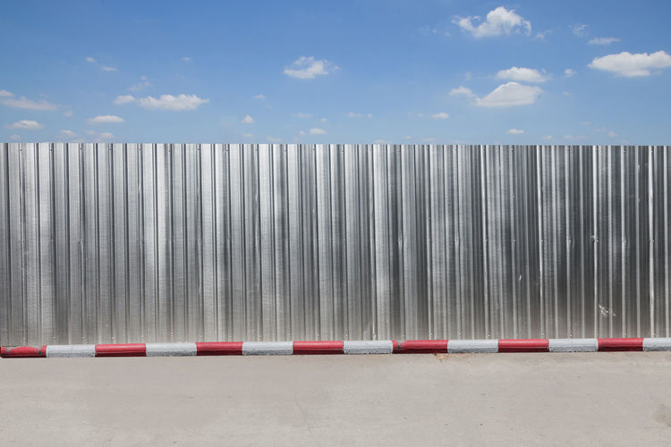 Corrugated iron by road against sky