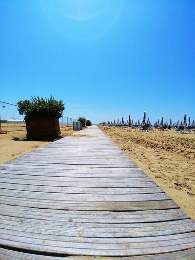 Boardwalk leading towards beach against clear blue sky
