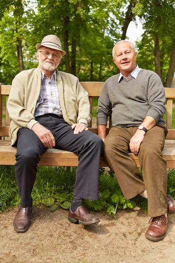 Portrait Of Male Friends Sitting On Bench