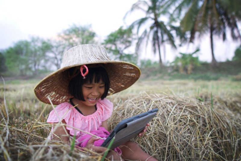 Smiling girl using digital tablet while sitting on field