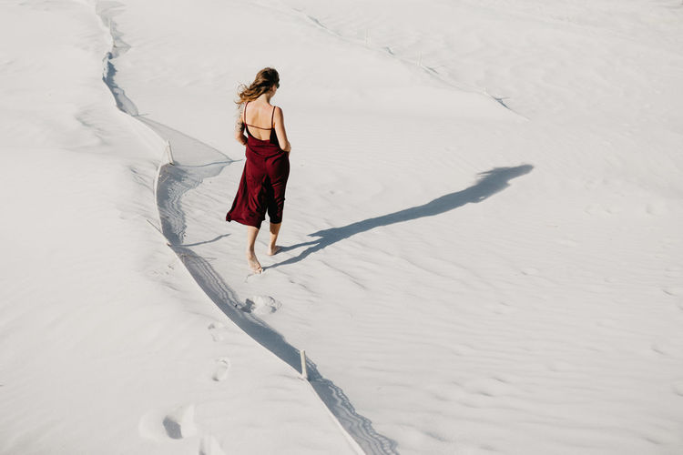 Rear view full length of young woman walking at sandy beach on sunny day