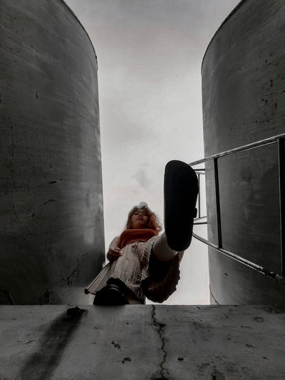 Rear view of woman sitting on wall against sky