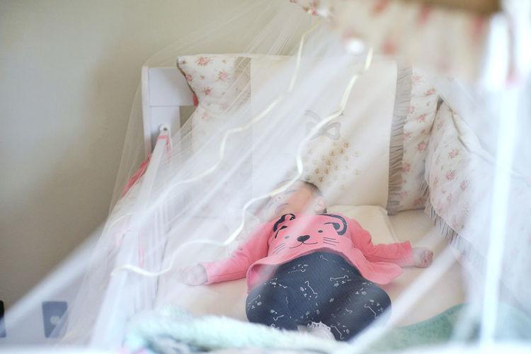 Cute baby girl sleeping in crib at home