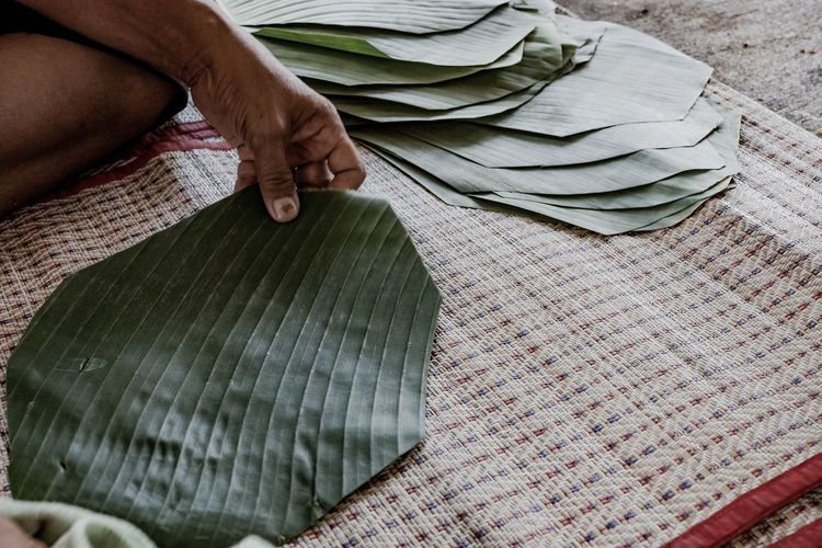 Midsection of man holding banana leaf while sitting on mat