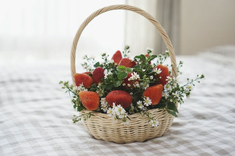 Close-up of strawberry basket on bed