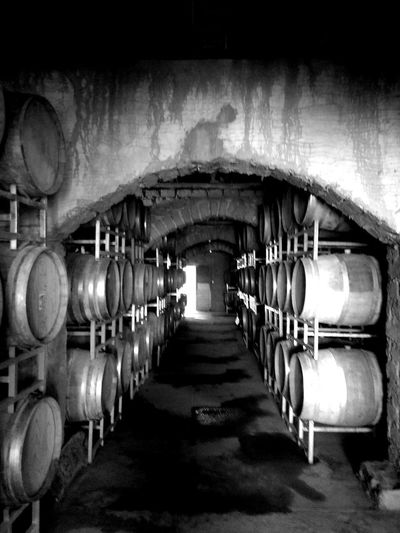 Bodega/Cellar In A Row Indoors  Cellar Wine Cellar Illuminated No People Food And Drink Large Group Of Objects Architecture Barrel Drink Building Winemaking Oenology Oenologist Order Cylinder Industry