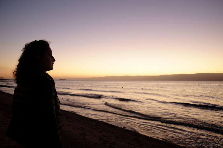 Red Sea One Person Sea Sunset Beach Sky Side View Land Water Adult Vacations Contemplation Trip Profile View Nature Scenics - Nature Beauty In Nature Horizon Tranquility Women Horizon Over Water Hairstyle Looking At View Hair Outdoors