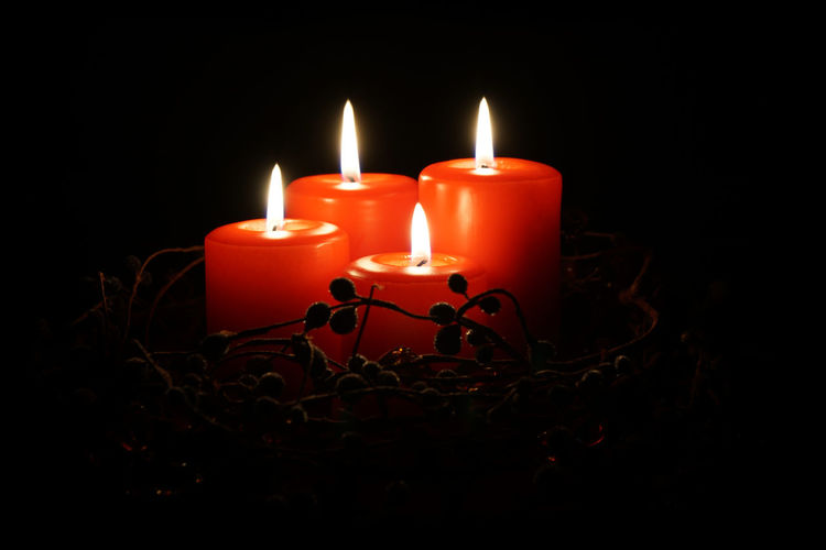 Close-Up Of Lit Candles Over Black Background