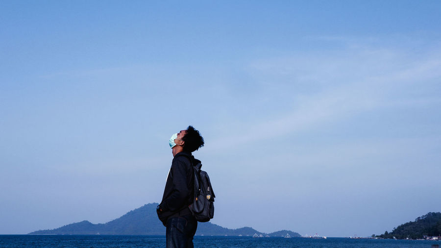 Side view of man standing with backpack at beach against sky