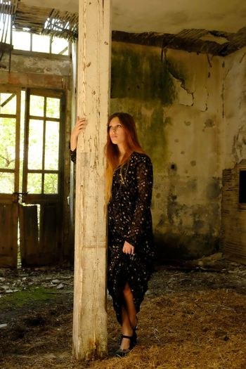 Thoughtful young woman standing while holding column in abandoned room