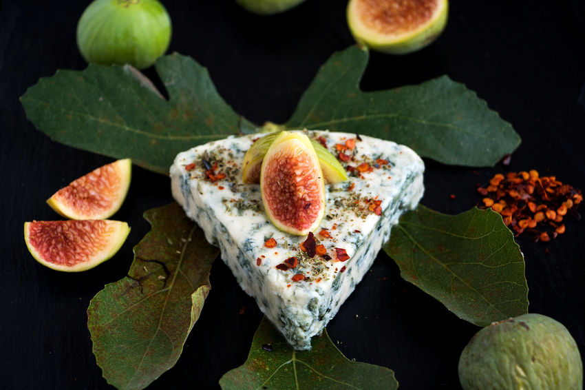 A piece of danish blue cheese on a fig leaf with green figs and peppers Danish Blue Cheese Aromatic Blue Mold Cheese Cheese Close-up Danablue Directly Above Fig Food Freshness Fruit Gorgonzola Cheese Healthy Eating High Angle View Indoors  Nature No People Noble Mold Mushrooms Roquefort SLICE Still Life Table Traditional Danish Christmas Food Triangle Wellbeing