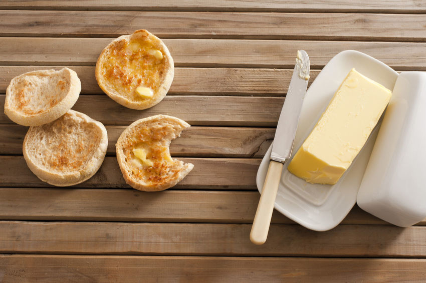 Freshly baked and toasted tasty crumpets, one bitten into, on a wooden table with a pat of butter on a plate, overhead view Above Baked Baking Batter Bitten Buttered Butterfly Cake Crumpet Dairy Food Food And Drink Freshness High Angle View Indoors  Knife Pattern Ready-to-eat Recipe Table Teatime Toasted Wooden Yeast