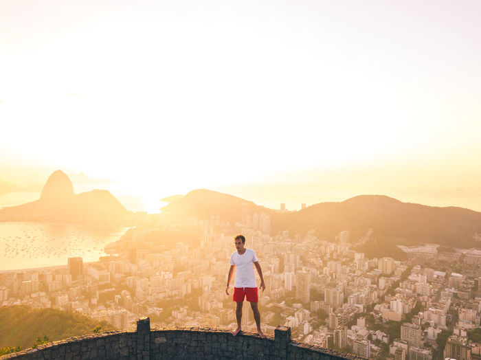 Full length of man standing in city against sky during sunset