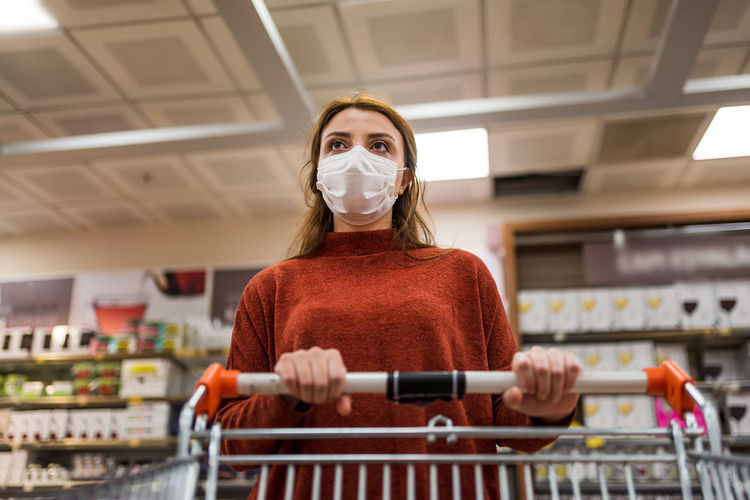 Low angle view of woman wearing mask at shopping mall