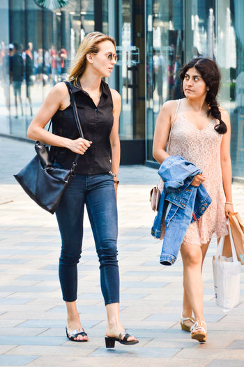 Beautiful Woman Casual Clothing City Consumerism Day Fashion Friendship Front View Full Length Happiness Jeans Leisure Activity Lifestyles Looking At Camera Outdoors People Portrait Purse Real People Smiling Standing Two People Walking Young Adult Young Women