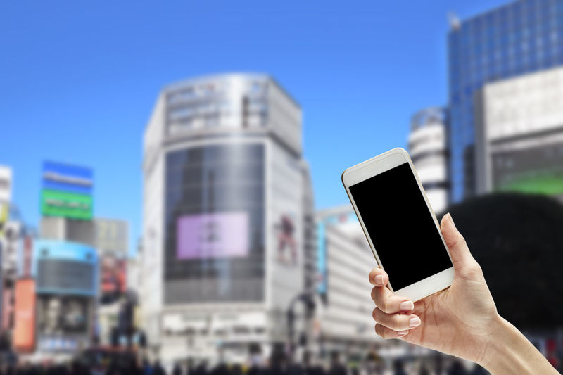 Close-Up Of Hand Holding Smart Phone Against City Buildings