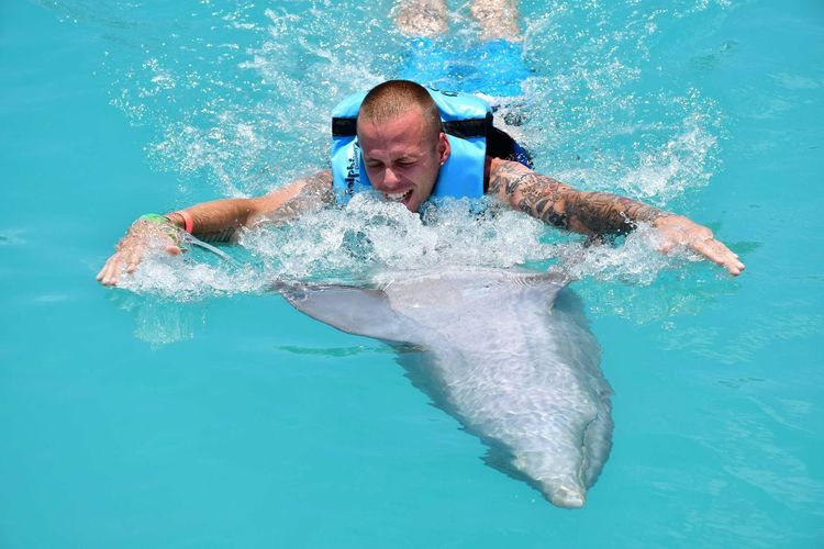Man swimming with dolphin in sea