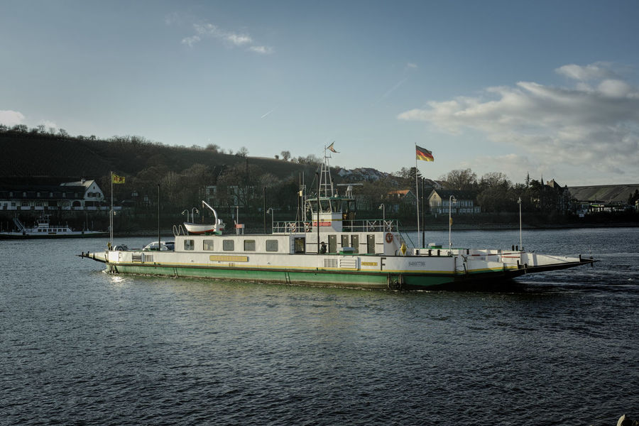 River Ferry Blue Boat Car Ferry Commuter Distant Ferry Ferryboat Geinsheim Mode Of Transport Nierstein Outdoors Rhine River River Ferry Traffic Transportation Travel Traveling Vacation Voyage Water Waterfront