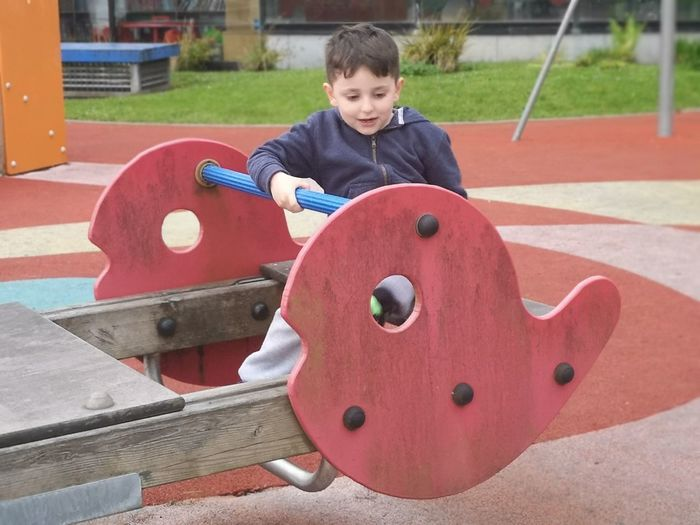 Cute boy playing on outdoor play equipment at playground