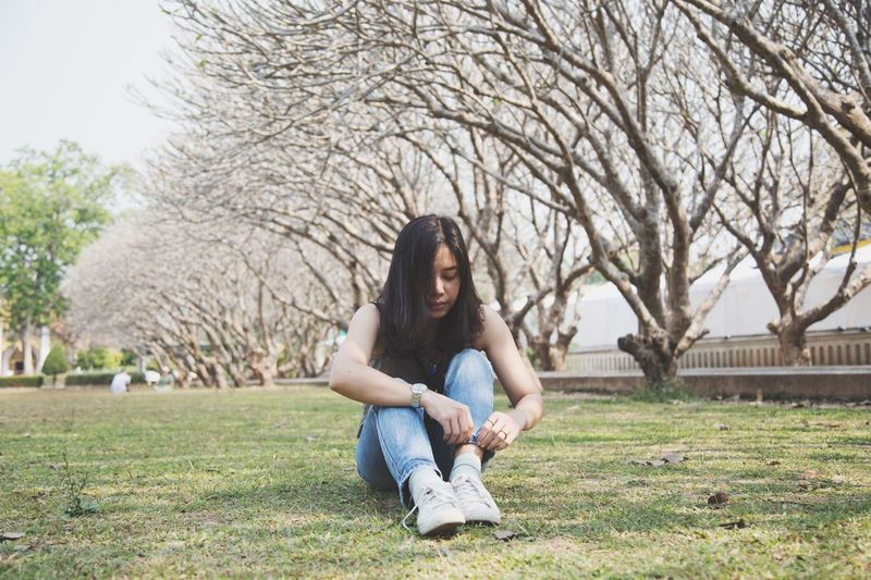 Full length of woman sitting on grass against trees