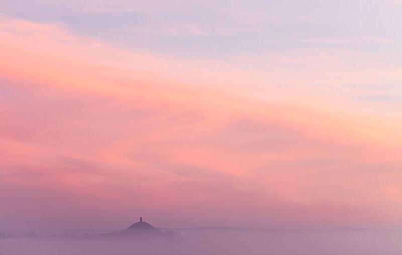 Scenic view of glastonbury tor against sky during misty sunrise