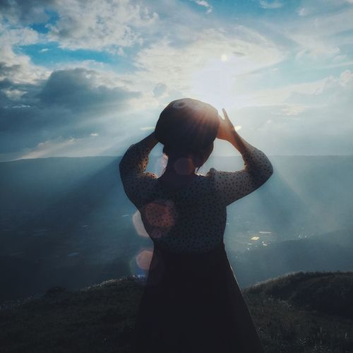 Rear View Of Woman Shielding Eyes While Standing On Cliff Against Cloudy Sky