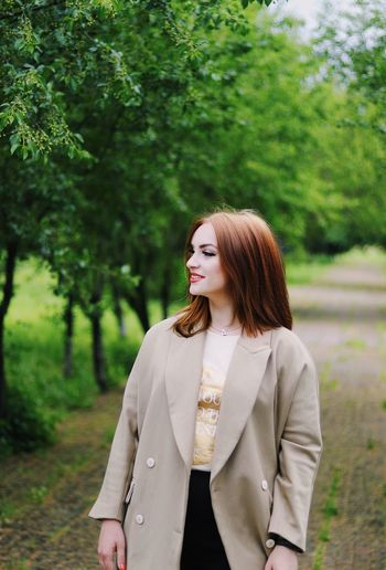 Young woman looking away against tree
