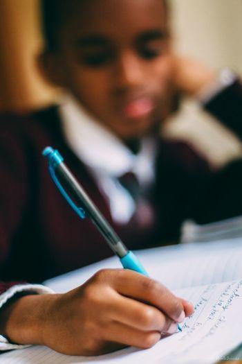 Close-Up Of Boy Doing Homework At Desk