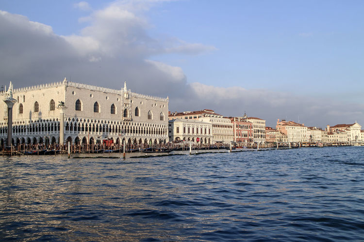 Doge palace by grand canal against cloudy sky