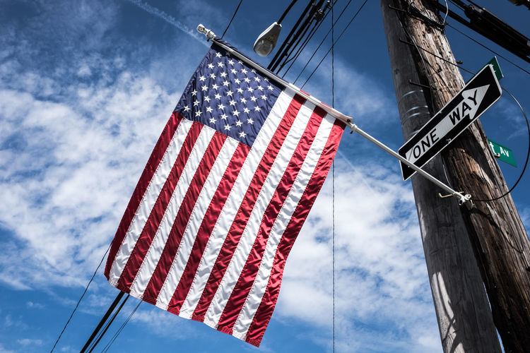 Low Angle View Of American Flag Against Cloudy Blue Sky