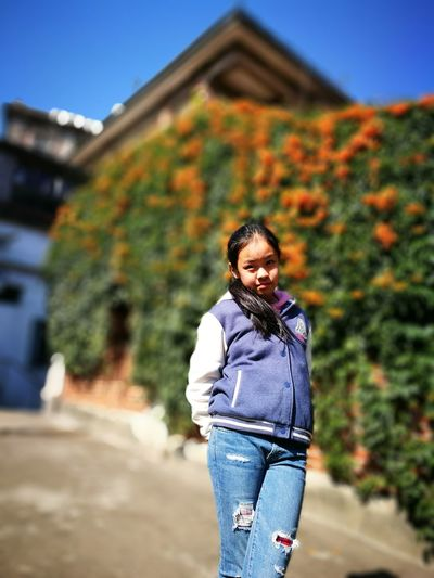 Portrait of girl standing against ivy on sunny day