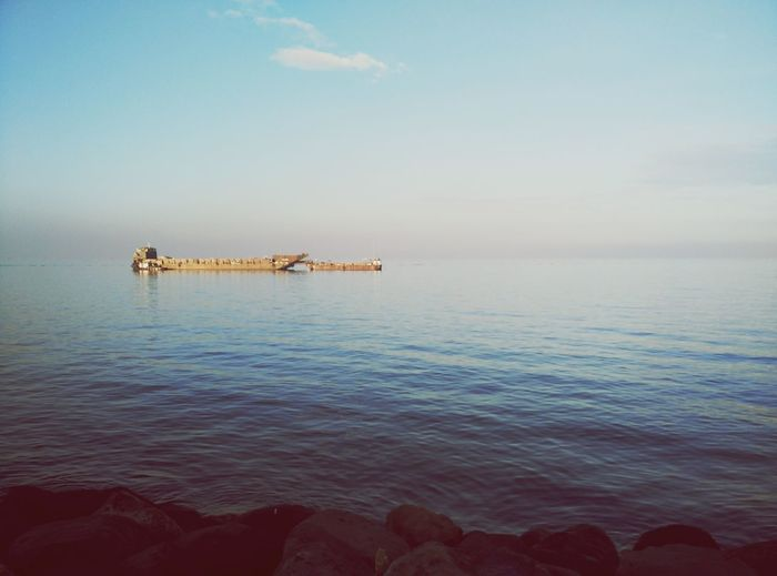 Barge amidst sea against sky