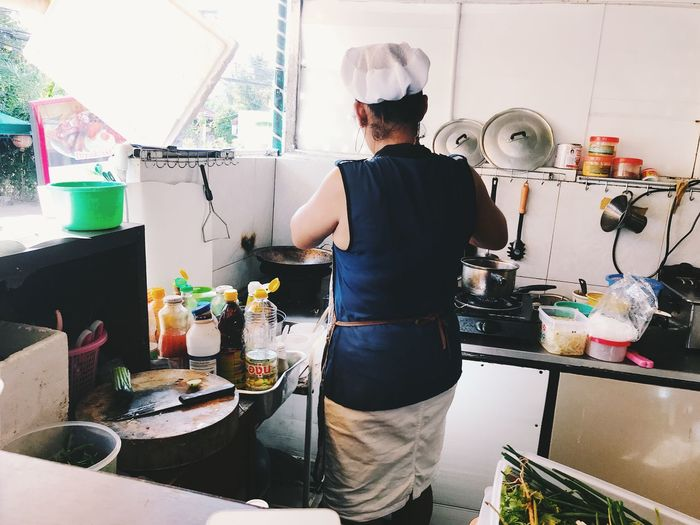 Rear view of man standing in kitchen at home