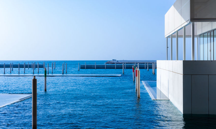 View of swimming pool by sea against clear sky