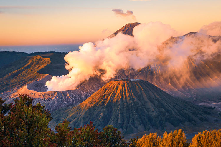 Panoramic view of smoke emitting from volcanic mountain against sky during sunset