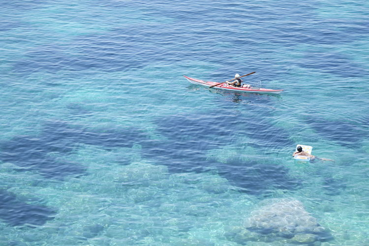 High Angle View Of People Swimming And Kayaking At Sea