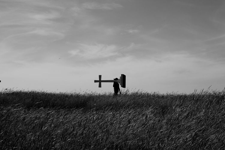 Person carrying cross on grassy field against sky