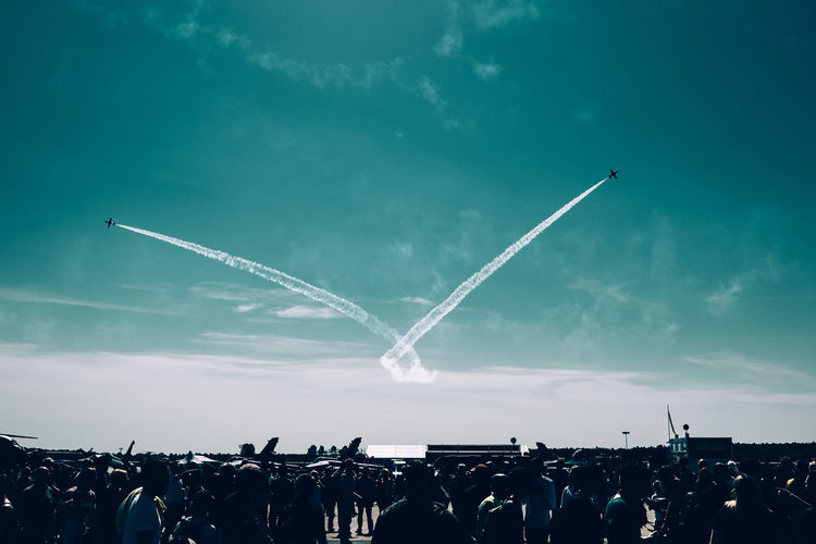Airplanes Flying Over People Against Sky