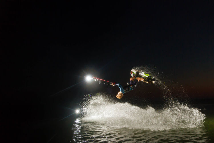 Silhouette of man fly boarding at night
