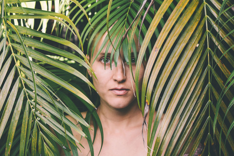 Portrait of woman amidst palm leaves