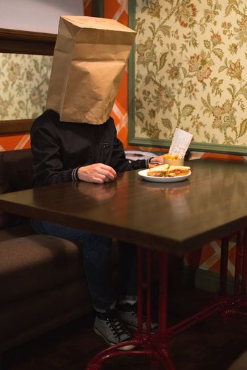 man with paper bag on his head eating a sandwich Diet Crazy Strange Sitting Bag On Head Hipster Sandwich Table Furniture One Person Men Indoors  Chair Food Males  Food And Drink