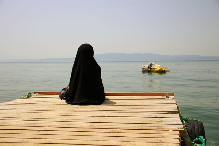 Rear view of women sitting on pier by sea against clear sky