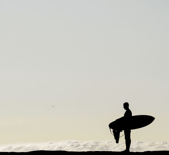 Silhouette man standing on shore against clear sky