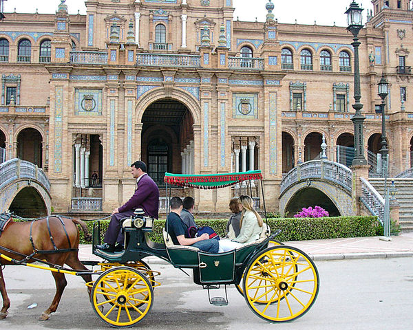 The Royal Palace at Seville, Spain Architecture People City Sitting Tourism Day History Outdoors Transportation Arch Adult Horse Cart Mammal Carriage Adults Only Horse Drawn Carriage Horsedrawn Travel Destinations Animal Themes Building Exterior Seville,spain Royal Palace Seville Yellow Wheels