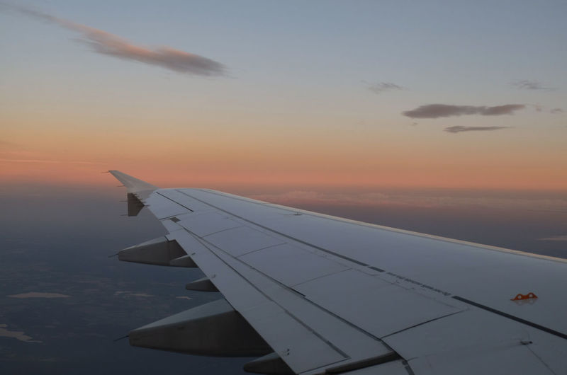 Cropped image of airplane flying over calm sea at sunset