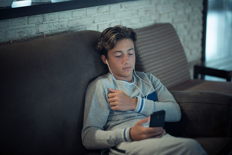 Teenage boy using smart phone while relaxing on sofa at home