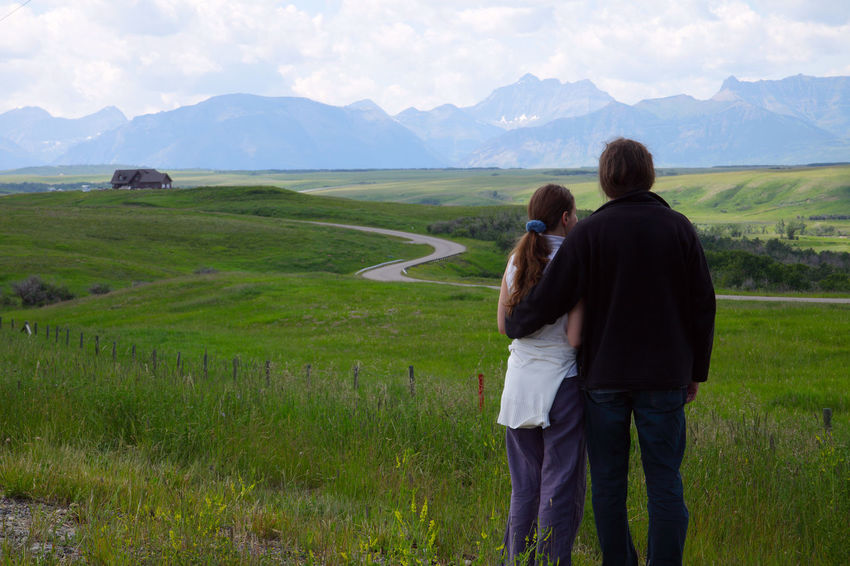 Couple enjoy the view of the Rocky Mountains (Alberta, Canada) Alberta Road Adult Beauty In Nature Bonding Canada Couple - Relationship Emotion Field Land Landscape Men Mountain Mountain Range Nature Outdoors Positive Emotion Real People Rear View Rocky Mountains Togetherness Travel And Tourism Travel Destinations Two People Women