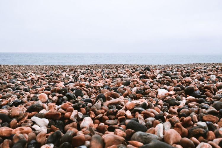 Pebbles on beach against clear sky